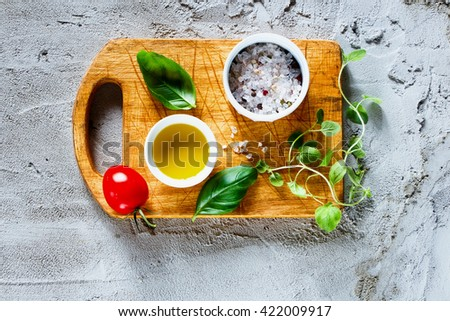 Cherry tomatoes with fresh basil leaves and olives oil on rustic wooden chopping board over concrete textured background, space for text. Italian food cooking ingredients. - stock photo