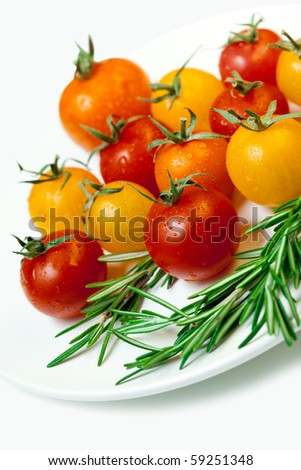 cherry tomatoes with rosemary on a white plate, isolated on white - stock photo