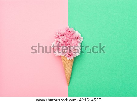 Cherry tree blossom in ice cream waffle cone on hipster colors background. Styled flat lay. Minimal concept - stock photo