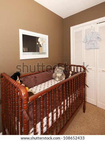 Cherry wood baby crib in nursery interior with brown wall. - stock photo