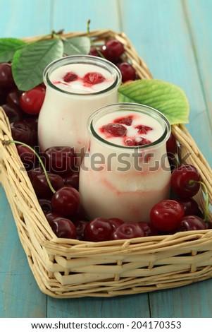Cherry yoghurt jar and fresh ripe cherries - stock photo