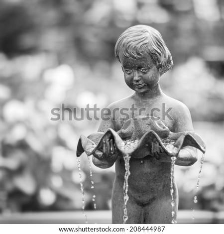 Cherub boy water fountain statue in garden  - stock photo