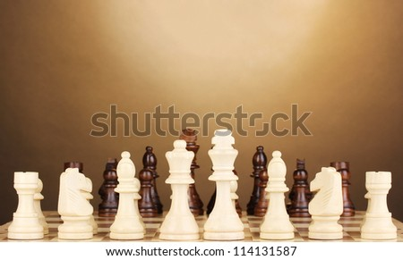 Chess board with chess pieces on brown background - stock photo