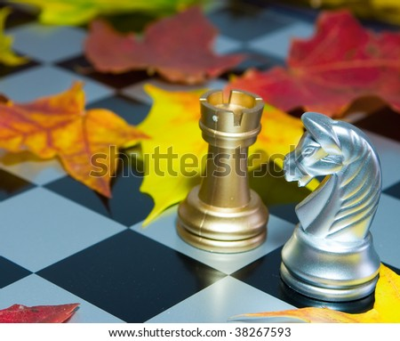 Chess combination on a board and autumn leaves - stock photo