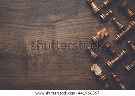 chess figures on the brown wooden table background - stock photo