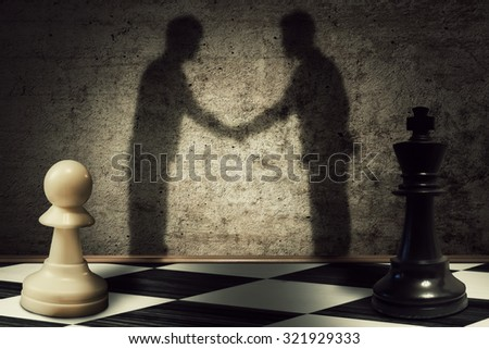 Chess pawn and king standing in front one another with their shadow transform into businessman giving handshake. Business hierarchy peace - stock photo