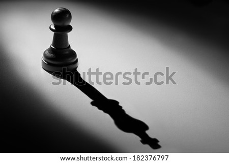 Chess pawn standing in a spotlight that make a shadow of king with darkness - stock photo