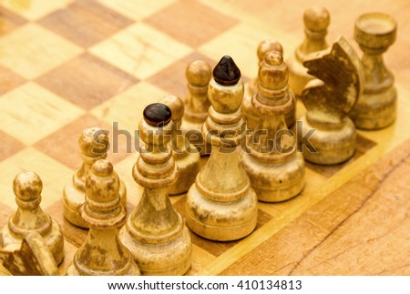 Chess photographed on a chessboard, on the street in the rain - stock photo