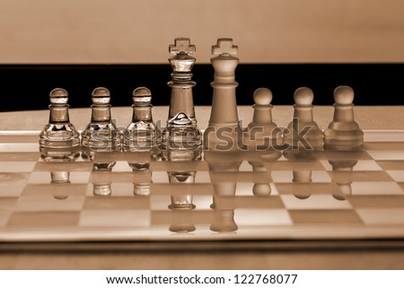 Chess Piece: King and pawns - business concept series: strategy, competition, business merger, leadership, business management, with reflections on chess board.  Sepia.  - stock photo