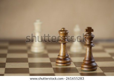Chess pieces and game board background; focus on queen (Shallow DOF) - stock photo
