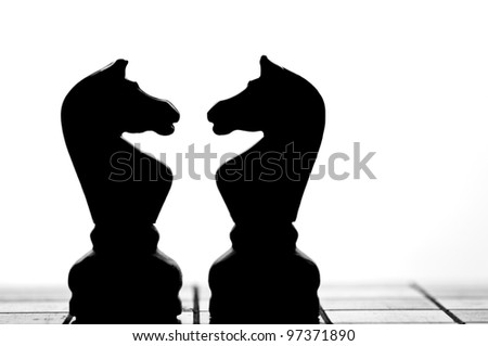 Chess pieces in conflict - stock photo