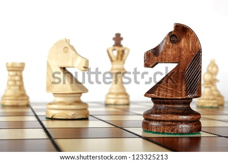 Chess pieces on a board (horse) - stock photo