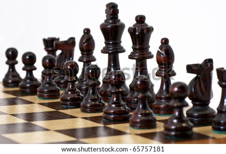 Chess pieces on a board with white background - stock photo