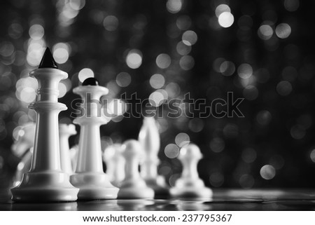 Chess pieces on black abstract background - stock photo