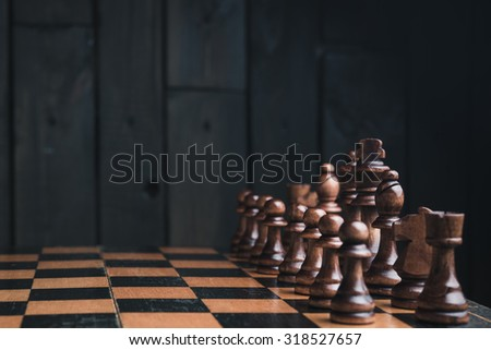 chess pieces on black wood background - stock photo