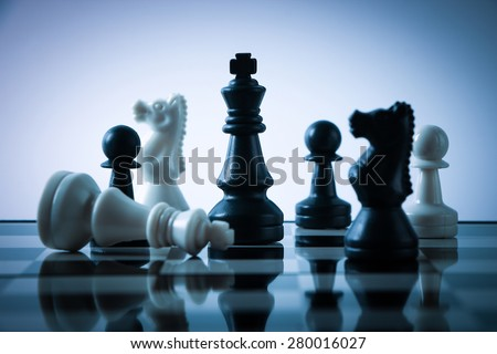 Chess pieces on board with gradually varied background. - stock photo