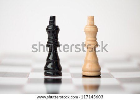 Chess pieces standing at the chessboard beside each other against white background - stock photo