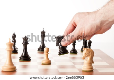 chess,white pawn surrounded by black chess pieces on a chess board - stock photo