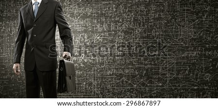 Chest view of businessman and chalk business sketches on wall - stock photo