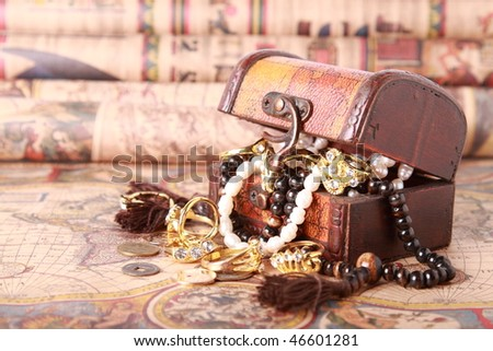 Chest with jewelry on antique map - stock photo