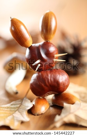 Chestnut and acorn figurine - bunny on wooden table. Selective focus, shallow DOF - stock photo