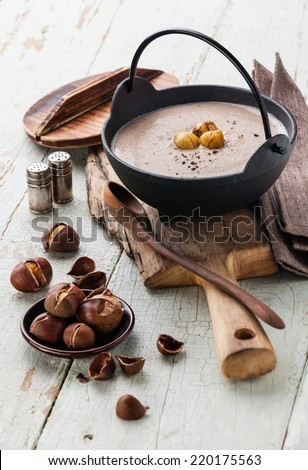 Chestnut soup in black iron pot with roasted chestnuts on blue textural background - stock photo