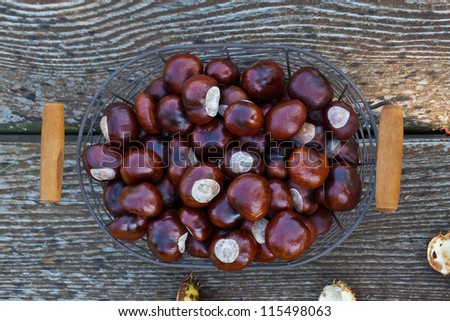 Chestnuts in a basket on wooden table - stock photo