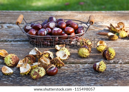 Chestnuts in a basket with skin on wooden table - stock photo