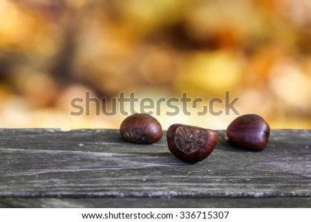 Chestnuts outside on wooden table - stock photo