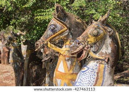 Chettinad, India - October 16, 2013: Ayyanar, village protector, Horse shrine of Namunasamudran. Two old clay horse heads are smiling. Painted bodies. - stock photo