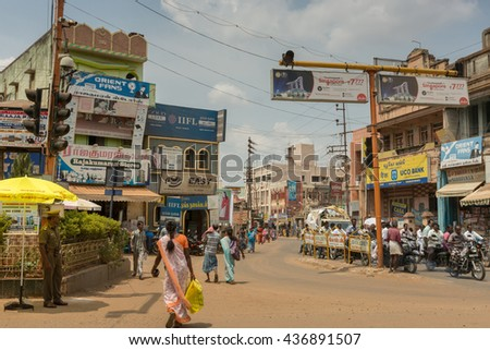 Chettinad, India - October 17, 2013: Busy intersection in Karaikudi city shows police, traffic, people, billboards, motorbikes, shops, and more. - stock photo