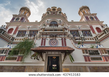 Chettinad, India - October 17, 2013: Chidambara Palace in Kadiapatti. Front view on facade shows towers, balconies, balustrades, the front entrance, Krishna decorations. Mainly beige and purples - stock photo