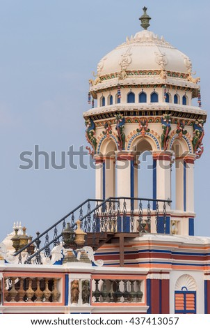 Chettinad, India - October 17, 2013: Chidambara Palace in Kadiapatti. View on lookout tower against blue sky. Combination of colors as decoration. - stock photo