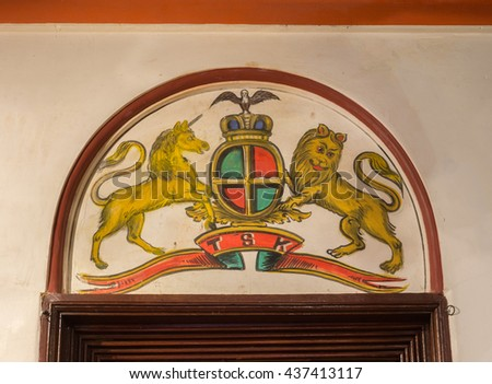 Chettinad, India - October 17, 2013: Chidambara Palace in Kadiapatti. Wall painting above door showing United Kingdom coat of arms. - stock photo