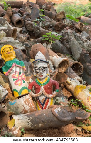 Chettinad, India - October 17, 2013: Kothamangalam Ayyanar horse shrine. Discarded brown clay figurines have two brightly painted examples intact. Figures used in pregnancy rituals.  - stock photo