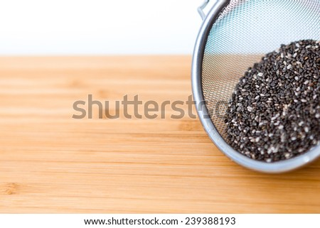 Chia seeds on wooden board - stock photo