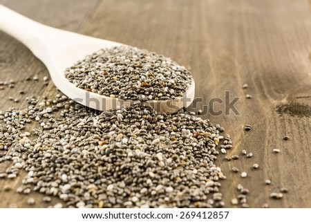 Chia seeds on wooden spoon and vintage wooden background - stock photo