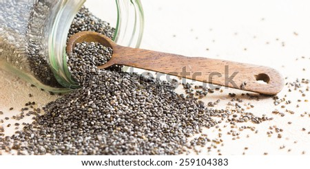 Chia seeds with wooden spoon on pink background - stock photo