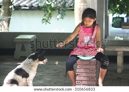 CHIANG MAI- JUNE 20  Unidentified little girl re divided food scraps to the dogs on JUNE 20 ,2009 at School in Chiang Mai Thailand ,This photo taken to the stories Little girl and dog - stock photo
