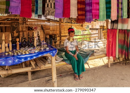 Chiang Mai, Thailand - April 24, 2009: A  lady waits for customer at her stall selling traditionally woven scarfs. The Karen tribe ladies are known to wear brass neck rings to extend the neck. - stock photo