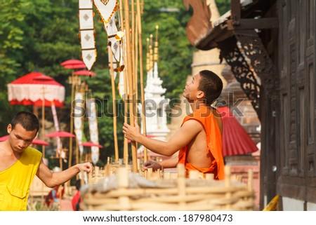 CHIANG MAI THAILAND - APRIL 17 : Songkran festival, Buddhist novice pins traditional flags on sand pagoda. APRIL 17,2014 in Phan-Tao Temple, Chiangmai, Thailand. - stock photo