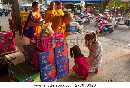 CHIANG MAI, THAILAND - APRIL 16, 2008: Unidentified Buddhist monks receive morning alms and food donations to their temple. Buddhism practices is widely seen and is an important part of life here. - stock photo