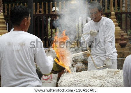 CHIANG MAI  THAILAND - AUGUST 12 : Buddhist metal cast ceremony for buddha statue , Pouring molten metal in mold for buddha statue . Aug 12,2012 in Lok Molee Temple, Chiangmai, Thailand. - stock photo