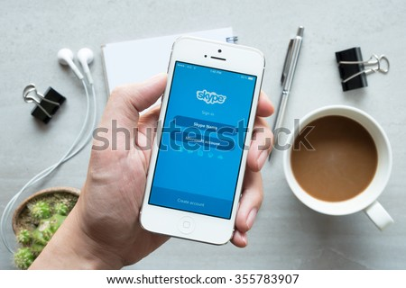 CHIANG MAI, THAILAND - DEC 20,2015: A man holds Apple iPhone with Skype application on the screen. Skype is an application that providing text chat, video chat and voice calls - stock photo