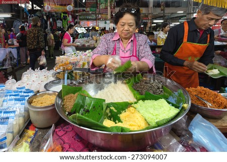 CHIANG MAI,THAILAND,DECEMBER 30,2014: A woman is selling different kind of sticky rices in the Talat Pratu market in Chiang Mai,Thailand - stock photo
