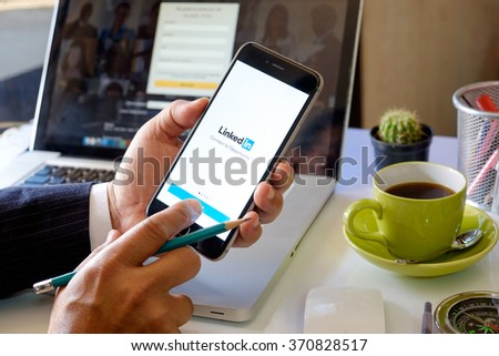 CHIANG MAI ,THAILAND FEB 2 2016 : Businessman holding a iPhone 6 plus with social network service LinkedIn on the screen. iPhone 6 was created and developed by the Apple inc. - stock photo