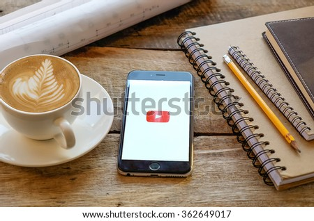 CHIANG MAI,THAILAND, JAN 15 2016 : Brand new Apple iPhone 6 plus with YouTube app on the screen lying on old wood desk with headphones. YouTube is the popular online video sharing website - stock photo