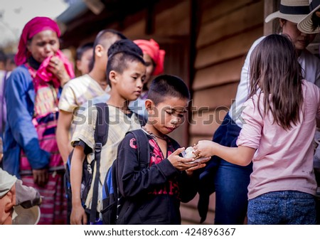 Chiang Mai Thailand -January,21,2016:A Girl from happiness family learn how to share the happiness by giving ice cream to a boy in remote area Karen village in remote area in Chiang Mai Thailand - stock photo