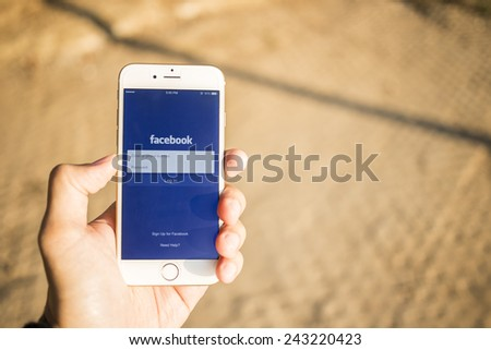 CHIANG MAI, THAILAND - JANUARY 04, 2015: A man trying to log in Facebook application using Apple iPhone 6. Facebook is largest and most popular social networking site in the world. - stock photo