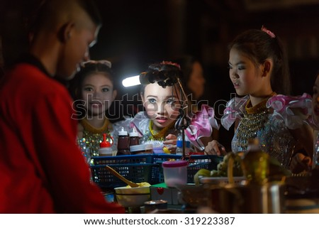 CHIANG MAI,THAILAND,JANUARY 04,2015 : A Thai traditional dancer little girl is ordering a banana pancake to the street seller during the saturday night market in Chiang Mai,Thailand. - stock photo